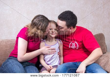 Mom and Dad kiss their daughter on the couch