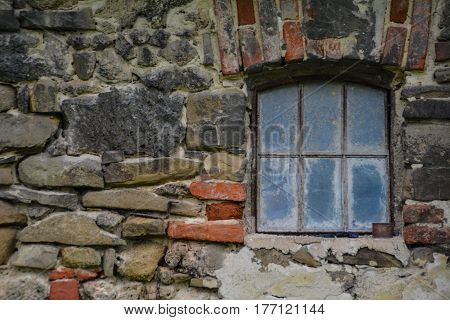 old wall with a glass window and colored bricks