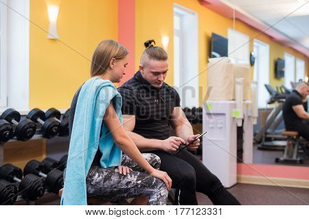 fitness, sport, exercising, technology and diet concept - smiling young woman and personal trainer with tablet pc computer in gym.