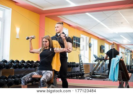 Working out in gym: Beutiful yong woman doing dumbbell excercise sitting on bench while muscular trainer watching and assisting her.