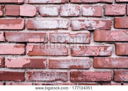 Red old brick wall with exfoliating paint, shabby background