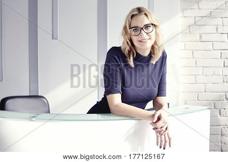 Beautiful blonde friendly woman behind the reception desk meet and smiling. Sunshine in modern office. Business conception working people