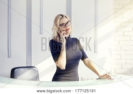 Beautiful blonde friendly woman behind the reception desk administrator talking by phone. Sunshine in modern office. Business conception working people