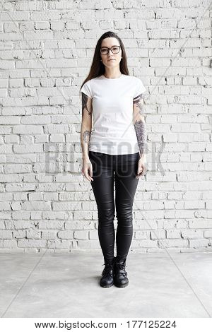 Young tattooed woman wearing blank t-shirt standing in front of brick wall in loft