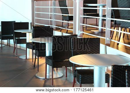 Tables and chairs on deck of cruise ship at night