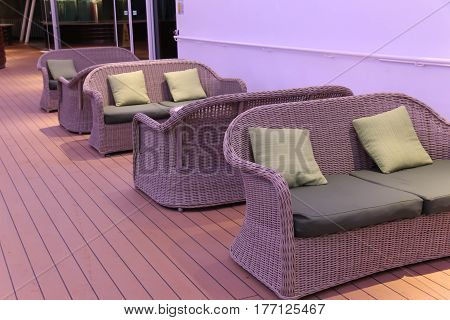 wicker love seats with cushions and pillows in low light on cruise ship deck