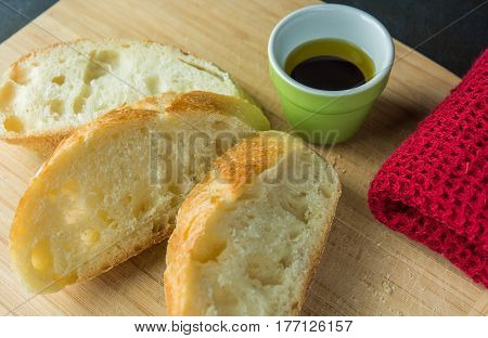 Slices of bread on cutting board with oil and cloth