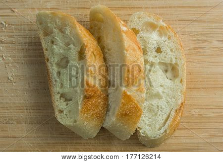 Three stacked baguette pieces on cutting board top view