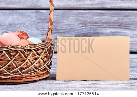Easter basket and empty card. Paper on wooden surface.