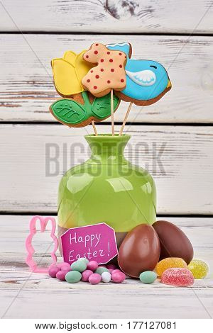 Easter greeting card and sweets. Confectionery on wooden surface. Easter present for sweet tooth.
