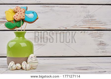 Styrofoam Easter eggs and vase. Colorful biscuits on sticks. Easter knocks at the door.