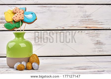 Vase and shiny Easter eggs. Three cookies on sticks. Congratulations for sweet tooth.