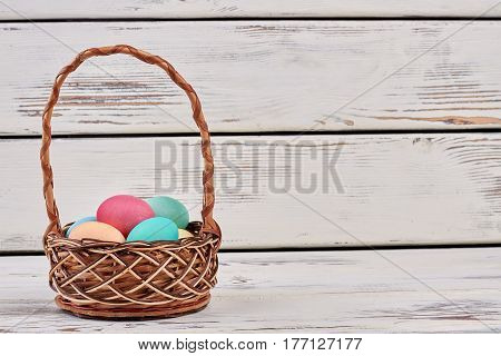 Basket with colored eggs. Wicker basket on wooden background. Simple Easter breakfast.