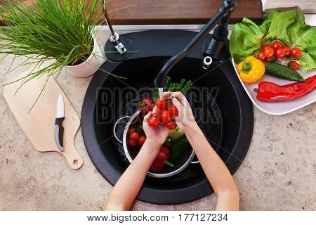 Child hands washing vegetables at the kitchen sink - top view with cherry tomatoes under the tap