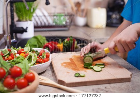 Child hands slicing a cucumber for a fresh vegetables salad - closeup on hands in a kitchen setting