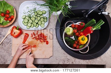 Child hands chopping vegetables for a salad - slicing the red bellpepper - top view of  the kitchen sink area with other ingredients