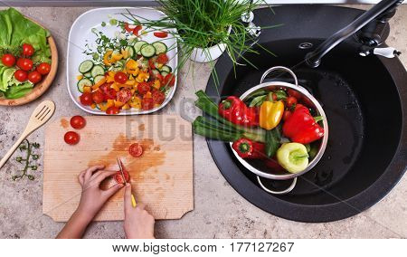 Top view of child hands slicing cherry tomatoes for a fresh vegetables salad - in the kitchen sink area with all the ingredients