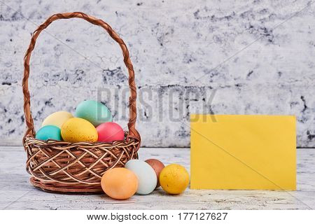 Basket with easter eggs. Blank yellow paper. Holiday of Christ.