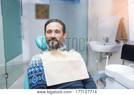 Person in dental chair. Mature man at the dentist. Consultation, diagnosis and treatment.