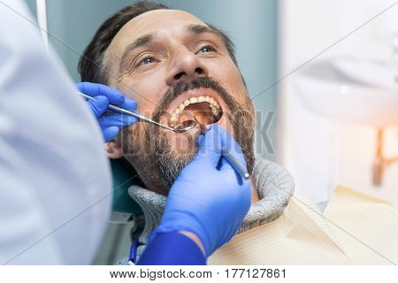 Adult man at the dentist. Doctor checking teeth. Precise dental diagnosis.