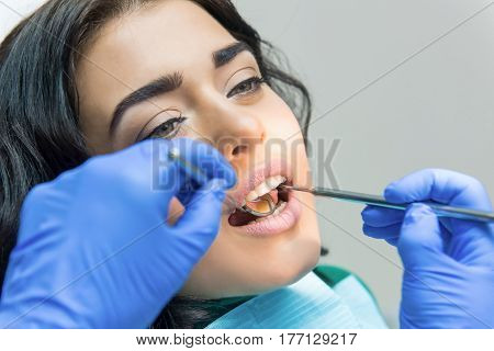 Young female at the dentist. Concave dental mirror.
