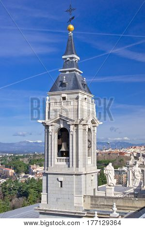Bell tower of Santa Maria la Real de La Almudena cathedral with Madrid city and Guadarrama mountains on background Spain