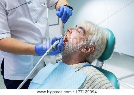 Stomatologist is cleaning teeth. Senior male at the dentist. Importance of hygiene for health.