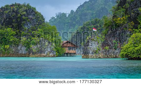 Bamboo Hut between some Rocks under Rain in Bay, Painemo Islands, Raja Ampat, West Papua. Indonesia