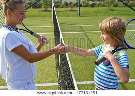 Tennis players shake hands before and after the tennis match. In the photo it looks like shaking hands greeting each other closely.