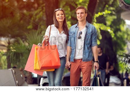 Happy couple with shopping bags walking and laughing