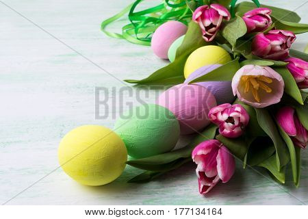Easter table centerpiece with pink tulips and pale color painted eggs