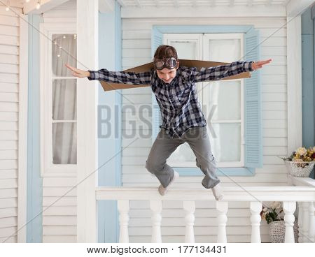 Happy boy jump with cardboard boxes of wings in home dream of flying