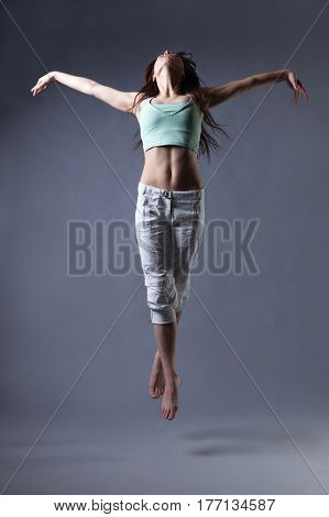 beauty girl dance on grey background. person jumping, flying in the air