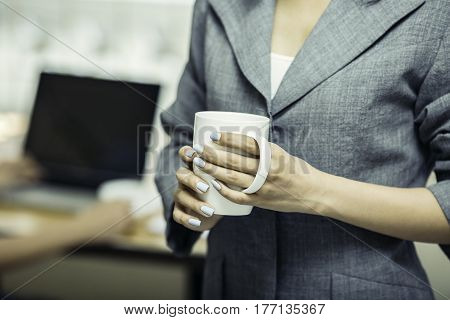 Part of woman body holding a coffee cup