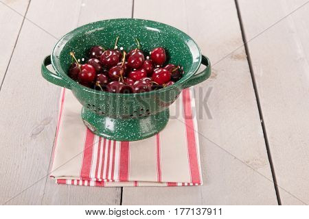 Fresh washed cherries in colander on wooden underground