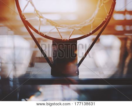 View from bottom of basketball hoop and basket with a lot of abstract reflections and aberrations around on summer sunny day with blurred beams of modern contemporary office stadium in background