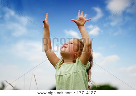 Cute little girl on the meadow in spring day. Child with arms outstretched. Freedom concept.