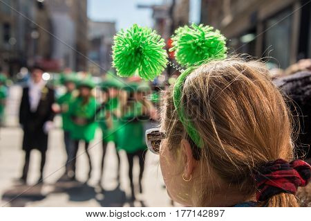 Montreal Canada - 19 March 2017: a female spectator wearing green head boppers is looking at St. Patrick's parade