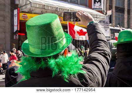 Montreal Canada - 19 March 2017: a spectator wearing a green hat is taking pictures of St. Patrick's parade