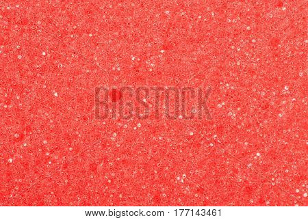 Close-up of a red cleaning sponge surface as a backdrop