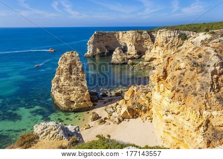 Boats with tourists visiting the beautiful beach of Marinha in Lagoa, Algarve Portugal