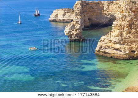 Boats with tourists visiting the beautiful Marinha beach, Algarve Portugal