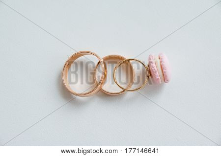 2 wedding ring together on white background and one small kids child girl ring like a symbol of love. Family wedding rings