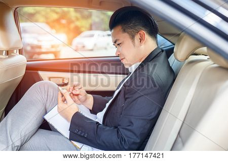 Handsome businessman sitting on backseat of car and touching telephone
