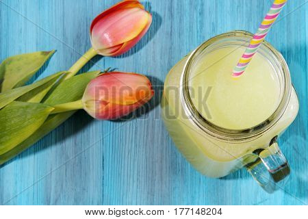 Lemonade in a mason jar with a few Tulips a refreshing Spring drink on blue wooden background.