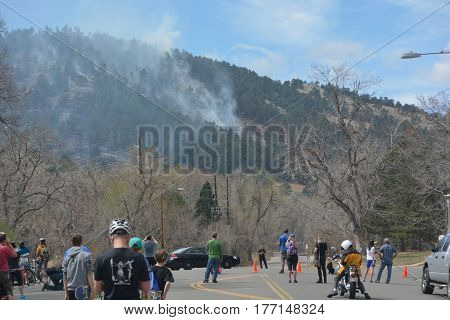 BOULDER CO USA - March 19 2017: Onlookers watch smoke rise from a forest fire in Sunshine Canyon immediately west of Boulder Colorado.