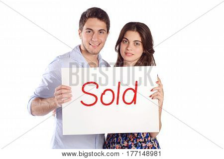 """Portrait of a young beautiful couple holding cardboard with """"sold"""". Isolated white background."""