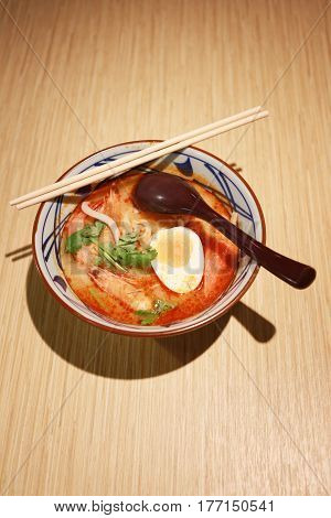 Ramen Tom Yum Goong of mix Thai foods and Japanese Food on wood background.