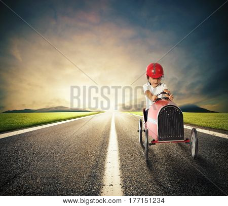 Child with a toy car drives on a country road