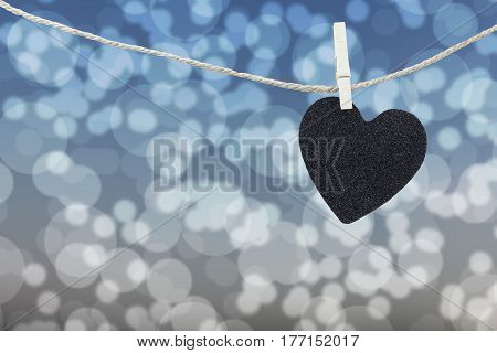 Black Heart hung on hemp rope on abstract colorful bokeh background and have copy space to manage the text you want.